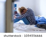 young woman crying in bed... | Shutterstock . vector #1054556666