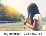 woman using mobile phone and... | Shutterstock . vector #1054561463