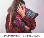 Small photo of A tired, elderly woman with long gray hair, presses a pillow on the white background