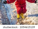 kid in yellow rainboots jumping ... | Shutterstock . vector #1054615139