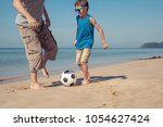 father and son playing football ... | Shutterstock . vector #1054627424