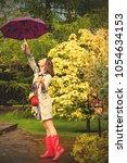 woman with an umbrella  wearing ... | Shutterstock . vector #1054634153