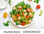 Chicken salad with vegetables on white wooden table. Top view, flat lay - stock photo