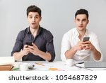 two shocked young men using...   Shutterstock . vector #1054687829