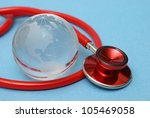 A stethoscope rests with a globe of earth for health concepts. - stock photo