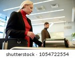 Small photo of Side view portrait of pretty blonde businesswoman swiping card passing turnstile to enter building