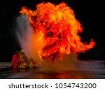 firefighter spray water to fire ...   Shutterstock . vector #1054743200