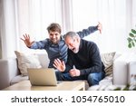 hipster son and his senior... | Shutterstock . vector #1054765010