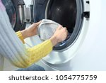 Young Woman Doing Laundry In...