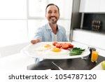 delightened mature man passing... | Shutterstock . vector #1054787120