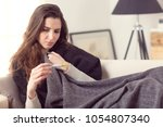 woman with flu virus sitting on ... | Shutterstock . vector #1054807340