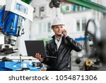 young engineer with laptop in... | Shutterstock . vector #1054871306