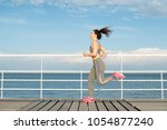 Small photo of Happy Latin fit girl running alone on bridge. Student in tracksuit keeping fit and enjoying available fitness. Solo run and free fitness concept