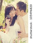 A couple with glasses of wine, a guy kisses a girl - stock photo