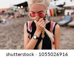 Stock photo shy blonde woman with braids posing at beach outdoor portrait of cute fair haired girl in pink 1055026916
