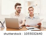 concentrated couple of young... | Shutterstock . vector #1055032640