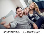 happy family taking selfie at... | Shutterstock . vector #1055059124