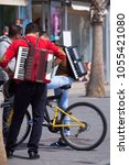 Small photo of Benidorm, Spain, 25/03/2018: Street musicians with an accordion on a bicycle.