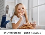 cute girl lies on window sill... | Shutterstock . vector #1055426033