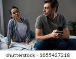 wife suspiciously looking st... | Shutterstock . vector #1055427218