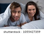 smiling man and woman lying in... | Shutterstock . vector #1055427359