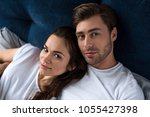smiling man and woman tenderly... | Shutterstock . vector #1055427398