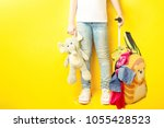 Small photo of baby girl getting ready for the journey. legs of the girl in jeans and a white T-shirt with a toy in her hand and a suitcase on a yellow background. Girl packs her bags. Dreams of travel.