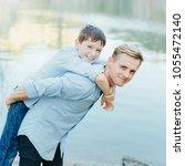 father piggyback his son... | Shutterstock . vector #1055472140