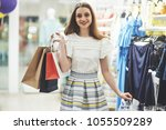 happy woman with shopping bags... | Shutterstock . vector #1055509289