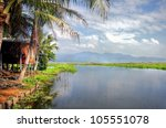 A tropical dream ; a gorgeous landscape by the lakeside with palmtrees and a wooden romantic cabin by the water - stock photo