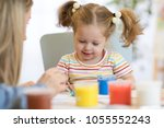 mom and kid painting together... | Shutterstock . vector #1055552243