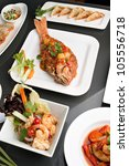 Freshly prepared Thai style whole fish red snapper sweet and sour shrimp gyoza dumplings sesame breads and other spicy Thai dishes. - stock photo