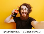 Small photo of 27/03/2018 Moldova Chisinau. Cheerful smiling bearded hipster man with Coca Cola Drink in hands. Man holding Coca Cola.