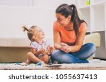 mother and daughter in their... | Shutterstock . vector #1055637413