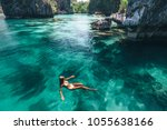 Young woman swimming in clear...