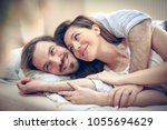 happy young couple in bed.... | Shutterstock . vector #1055694629