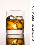 Small photo of glass of delicious whiskey with slices of ice on a gray background concept of an elite alcoholic beverage