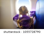 Small photo of Adorable little girl traveling by an airplane. Child sitting by aircraft window and looking outside. Traveling with kids abroad.