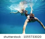 Small photo of Underwater selfie with a stick of young adorable charming adventuristic love student couple diving and relaxing with goggles in the exotic turquoise sea at summer vacation.