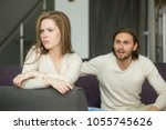 Small photo of Unhappy young couple arguing, offended affronted woman ignoring angry man sitting her back to jealous husband shouting at frustrated wife, family fight at home, bad marriage relationships concept