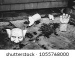 Small photo of Creepy black and white gargoyle smashed on floor
