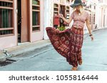 boho girl in maxi skirt walking ... | Shutterstock . vector #1055816444