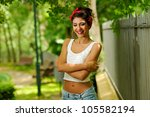 Portrait of a pin-up girl. American style, in a garden, wearing jeans and t-shirt - stock photo