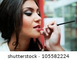 Professional makeup with a beautiful young woman having touches applied to her make up by a beautician - stock photo