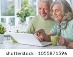 happy senior couple with laptop ... | Shutterstock . vector #1055871596