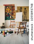 Small photo of Painting studio interieour. Easer, chair, colors and paintings all around.