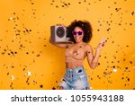 Small photo of Hey what's up! Join the get-together! Cool carefree attractive reckless crazy female party-goer is holding a stereo boombox on a shoulder and showing v-sign, isolated on yellow background