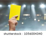 hand of referee with yellow... | Shutterstock . vector #1056004340