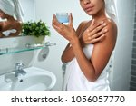 Small photo of Cropped image of woman applying body butter afther taking a bath