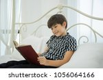 Young Boy Reading Book On Bed...
